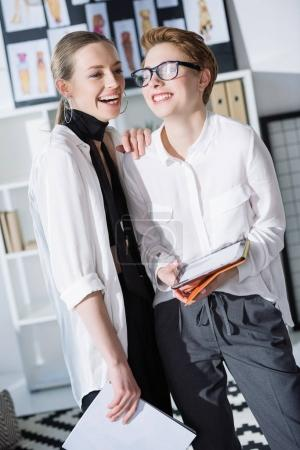 laughing young businesswomen using digital tablet together