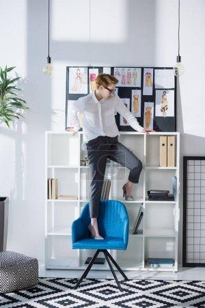 Photo pour Stylistique attrayant créateur de mode debout sur la chaise au bureau - image libre de droit