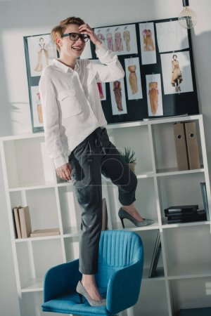 happy attractive fashion designer standing on chair at office