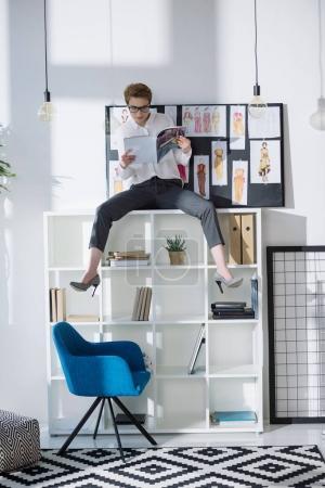 Photo for Stylish fashion designer sitting on bookshelves and reading magazine - Royalty Free Image