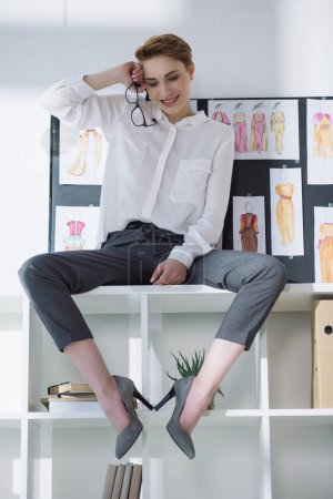 beautiful stylish fashion designer sitting on bookshelves