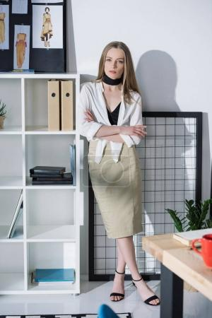 attractive fashion designer leaning on bookshelves at office