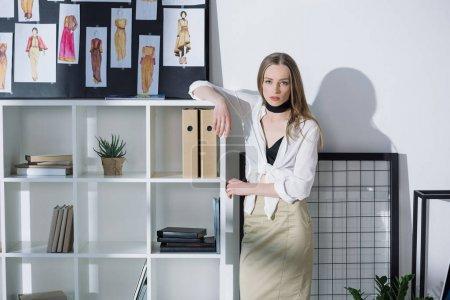 stylish fashion designer leaning on bookshelves at office