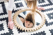 attractive young woman looking at camera through mirror reflection
