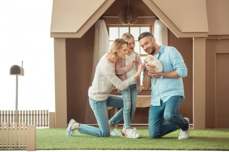 happy family with adorable labrador puppy in front of cardboard house