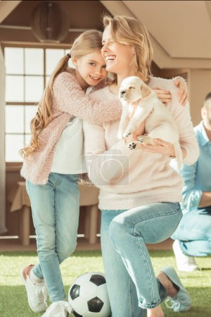 smiling mother and daughter playing with adorable labrador puppy