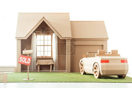 Photo for Cardboard house and car with sign sold isolated on white - Royalty Free Image