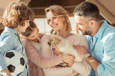 young family with adorable labrador puppy in front of cardboard house