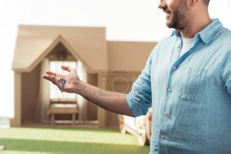 homme heureux tenant la clé de la nouvelle maison en carton isolé sur blanc