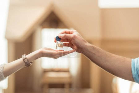 cropped shot of real estate agent passing key to client