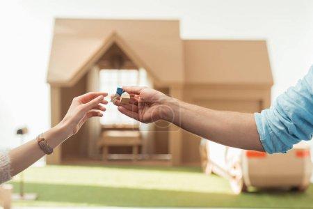 Photo pour Recadrée tir d'agent immobilier en lui passant key au client en face de la maison en carton - image libre de droit