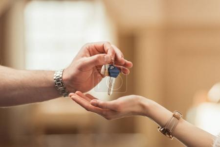 Photo pour Plan recadré de l'agent immobilier passant la clé au client - image libre de droit