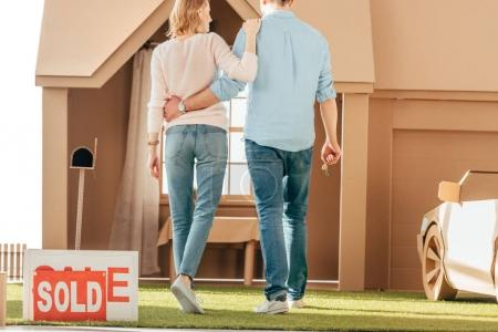 rear view of newlyweds walking to their new cardboard house