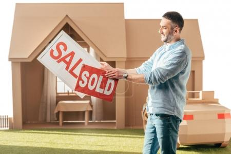 Photo for Man holding sale and sold signboards in front of cardboard house isolated on white - Royalty Free Image