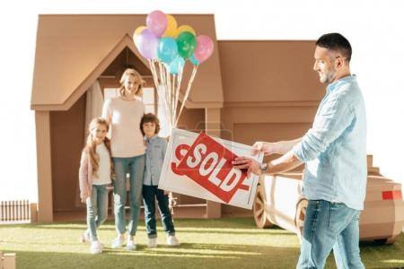 happy young family moving into new cardbord house isolated on white