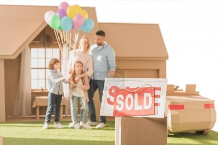 sold signboard with young family on yard of their new cardbord house blurred on background isolated on white