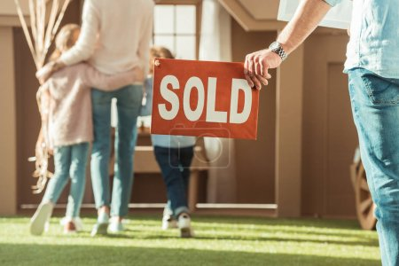 cropped shot of man holding sold signboard with young family moving into new cardbord house
