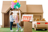 kid presenting balloons to girlfriend in front of cardboard house with sold signboard on foreground isolated on white