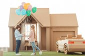 kid presenting balloons to girlfriend in front of cardboard house isolated on white