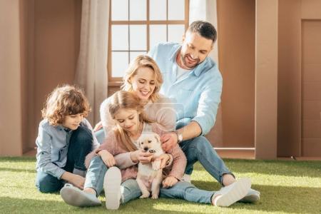 Foto de Hermosa joven familia con cachorro labrador amarillo en yarda de la casa de cartón - Imagen libre de derechos