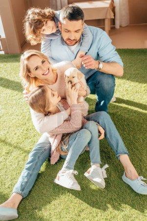 Foto de Familia joven feliz con cachorro de labrador en el patio de la casa de cartón - Imagen libre de derechos