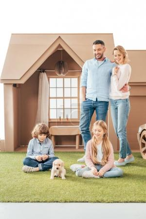 young family with cute puppy on yard of cardboard house isolated on white