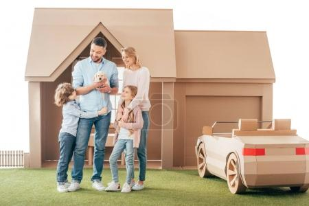 young family with adorable puppy on yard of cardboard house isolated on white