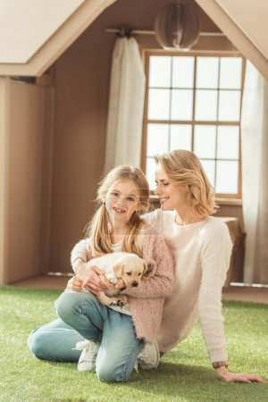 happy mother and daughter embracing with adorable labrador puppy in front of cardboard house