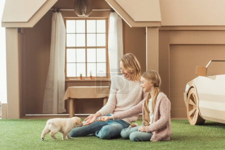 mother and daughter playing with adorable labrador puppy in front of cardboard house