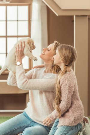 mother and little daughter playing with adorable labrador puppy