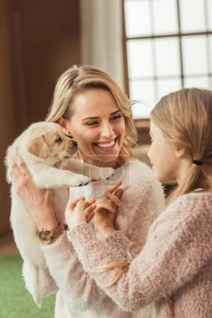 beautiful mother and daughter playing with adorable labrador puppy