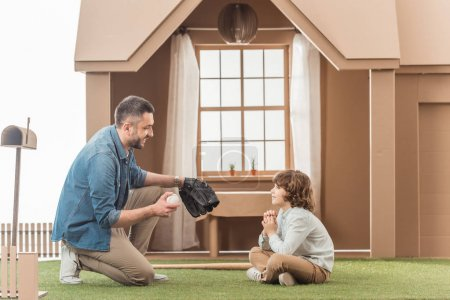 father teaching his son how to play baseball on grass in front of cardboard house