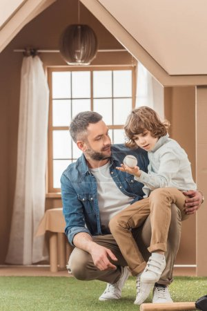 happy father teaching his son how to play baseball in front of cardboard house