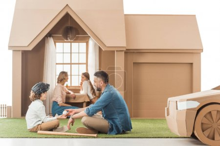 beautiful young family spending time together at cardboard house isolated on white