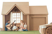 father playing guitar for kids and wife at new cardboard house isolated on white