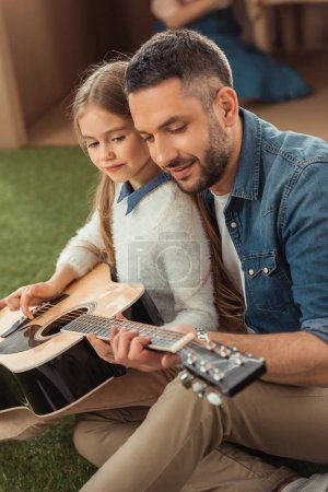 Photo for Happy father and daughter playing guitar while sitting on grass - Royalty Free Image