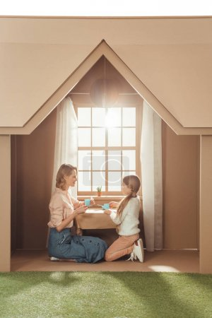 beautiful mother and daughter having tea party in cardboard house