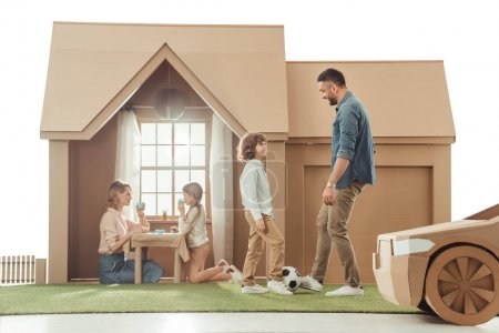 young father teaching his som to play soccer on yard of cardboard house isolated on white