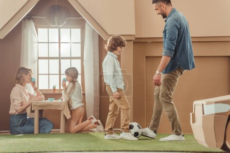 happy father teaching his som to play soccer on yard of cardboard house