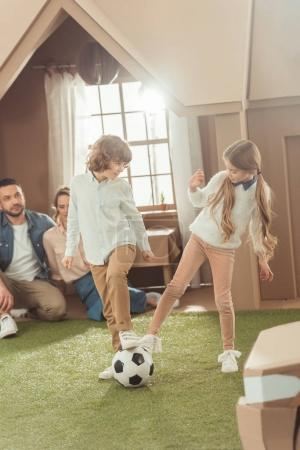 siblings playing football on yard of cardboard house while parents looking at them