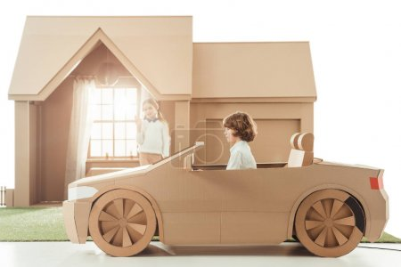 Photo for Kid riding cardboard car in front of house while girlfriend waving to him isolated on white - Royalty Free Image