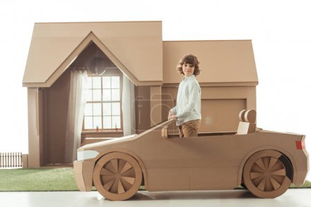 Photo for Little kid standing in cardboard car in front of cardboard house isolated on white - Royalty Free Image