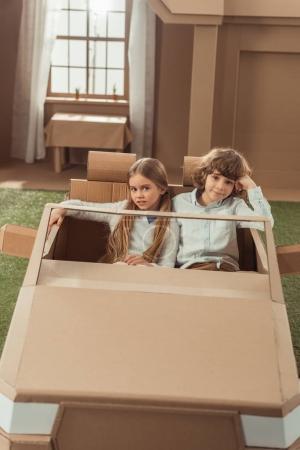 adorable kids couple riding cardboard car
