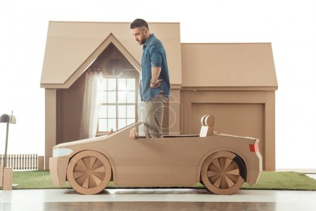 side view of man in cardboard car in front of cardboard house isolated on white