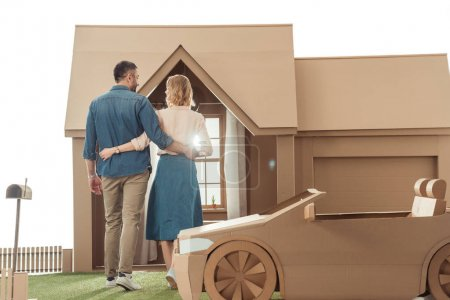 rear view of couple embracing in front of cardboard house isolated on white