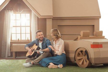 Foto de Hombre tocando la guitarra para novia en patio de casa de cartón - Imagen libre de derechos