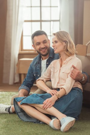 couple relaxing on yard of cardboard house
