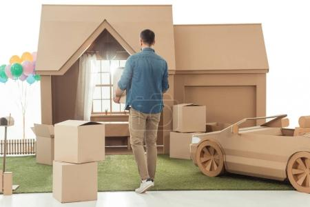 rear view of man with boxes moving into new cardboard house isolated on white