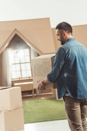 man with boxes moving into new cardboard house