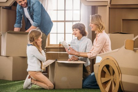 Photo for Young family unpacking boxes while moving into new cardboard house - Royalty Free Image